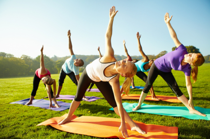 Energetic group of a young yoga class performing stretches outdoors on a sunny day